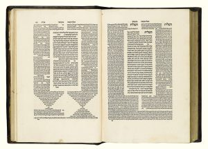 Two pages of a 16th-century Talmud (Tractate Me'ilah, sixth perek). The Hebrew letters of the Talmud are arranged at the center of each page in a column, surrounded by two columns of commentary text on each side. In the left page, the commentaries conclude at the bottom of the page in an hourglass formation of text.
