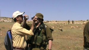 In a mild desert landscape, a man in a yellow shirt and white baseball cap and holding a blue backpack points a camera in the face of another man. The other man is dressed in army greens and points a camera in the face of the man in the yellow.