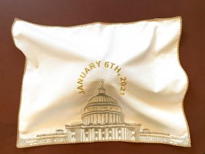 """A brocade challah cover with gold trim is on a reddish brown background. The challah cover is brightly lit and is propped up by the challah that it covers underneath. The challah is not visible. The fabric is white and the US Capitol is embroidered in gold in the center. Above the Capitol, """"JANUARY 6TH, 2021"""" is embroidered in gold in a circular shape above and around the Statue of Freedom. Below the dome, the hebrew phrase חדש ימינו כקדם is embroidered in gold."""