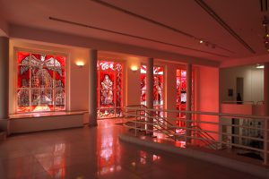 The gallery viewed from the upper level, red light flooding through the windows and into the space.
