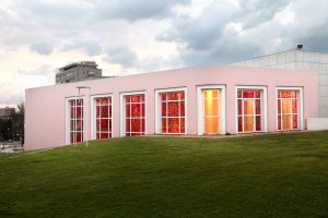 The exterior of the gallery viewed during the day. Sunlight penetrates into the gallery through the windows and the interior is visibly red from the outside.