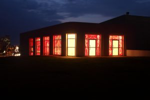The exterior of the gallery viewed at night. The gallery glows red, thanks to the artificial light inside the gallery and the darkness that covers it from the outside.