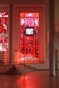 """The first window depicts a sort of an expulsion scene painted in deep red. At the center of the window is an open book with Hebrew text written on both sides (quoted from 'Ro'achem,' a book the artist wrote about seven years earlier). On the right side, the text is written as normal, from right to left, but on the left side, it is written in mirror to the other side, from left to right. Next to the image of the book, on both sides of it, appear two semi-human figures, both pointing at it with their hands. Their feet look like the legs of a beast. Above the image of the book, two angels appear, facing each other, also gesturing toward the book below. Above the angels, at the top of the painting, there is a big eye with curved rays coming out of it and a light bulb within — a reference to Picasso's """"Guernica."""" Underneath the book and coming down from it is a ladder that gets more and more narrow as it goes down to the bottom of the window. On the ladder is a figure of a naked and hairy man climbing downward. At the bottom of the window there is a winding tangle of tails and scales, headless and lacking any other organs."""