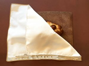 A brocade challah cover with gold trim is on a reddish brown background. The challah cover is brightly lit and the upper right hand corner of the cover is folded open revealing a braided challah underneath. The challah is on a brown cutting board with numerous knife marks. At the bottom of the challah cover, a small section of the Capitol Building is visible under the folded fabric.