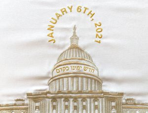 """A detail photograph of a brocade challah cover. The fabric is white and the US Capitol is embroidered in gold in the center. Above the Capitol, """"JANUARY 6TH, 2021"""" is embroidered in gold in a circular shape above and around the Statue of Freedom. Below the dome, the hebrew phrase חדש ימינו כקדם is embroidered in gold."""