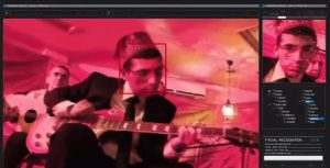A man, Avishai, wearing a suit, glasses, and decorated red fez plays a guitar. We are looking at him through a series of surveillance screens, which cast everything in pink. A small red box outlines his face and to the right a computer screen zooms in. It all looks very forensic. They are identifying his face.