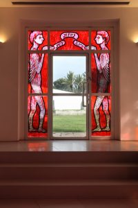 """The fifth window — one of the two windows on the upper floor surrounding the exit doors leading to the university campus — shows the (doubled) image of the snake after it had received back its hands, legs, and wings. It now looks like a human covered in reptilian scales. These two figures stand on both sides of the door and hold together a kind of a ribbon that quotes a sentence from 'Ro'achem': """"And you shall be like leeches to knowledge."""""""