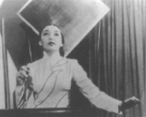 Blurred black-and-white photograph of Clara Rockmore playing the theremin. She stands before the black, waist-high electronic instrument as if before a keyboard, long dark hair stroked tight back behind her head, dark eyes and lips pointed up, wearing a light full-sleeved gown. Her right hand is lifted up before her right shoulder, gripping a small black electronic device, while her left hand hovers out beyond the left end of the theremin. The shadows of electronic cables or the cables themselves cross her upper body, perhaps connected to the device in her right hand.