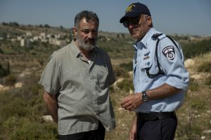 A middle-aged man in plain clothes, Hussein, is on the left side of the image while Avi Levi, a police official in uniform, discusses with him to the right. A landscape of Jerusalem hills fills the background.