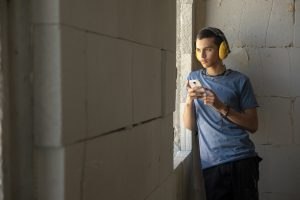 A young teenager, Muhammad, leans against a cement wall while holding a cell phone. He looks out a window in the wall, but what he is looking at is not visible. The walls look unfinished and Muhammad wears yellow construction earmuffs.