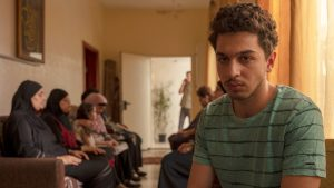 A young man, maybe late teens or early 20s with curly hair and a very light moustache and beard appears to be watching something, maybe a TV, that is not shown. Behind him sit about 6 women in hijab on a couch and looking down or with their eyes closed.