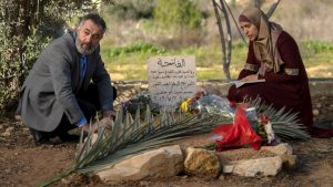 A middle-aged man, Hussein, crouches down at the left side of a grave. He wears a gray suit with a bright blue shirt. A woman crouches on the opposite side of the grave — Suha, Muhammad's mother. She wears a scarlet red thobe and a beige hijab. There are flowers around the grave and Suha rests a book in her crouched lap.