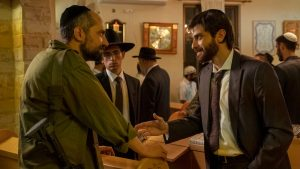 The setting appears to be a synagogue. On the left, a man, Simon, is wearing a kippah and an army uniform with a gun hanging off his arm. He's talking to another man, Yosef ben Haim, who is wearing a suit, tie, and kippah and who holds out his hand towards Simon to shake it. A younger man, Avishai, in a black hat looks on. In the background, there are a number of men in the synagogue, diversely dressed; some wear black hats and others wear white kippot.