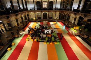 The camera looks down on a large, inner court of an exhibition hall. At the center is a table surrounded by scholars. The flooring is made of thick strips of green, red, white, and orange. An arched hallway lines the court and is lit from within.