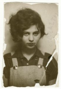 Old, rectangular and sepia-colored photograph of a young Mascha Kaléko staring directly at the viewer. The edges of the photograph are torn or rotted off, while a tear cuts across the bottom-right corner, down through her shoulder. Kaléko has very thick, wavy dark hair, the whole of which is combed entirely to the right side of her head, framing the side of her face. She wears grey, perhaps wool overalls, and a darker colored short-sleeved, collared shirt beneath. Her gaze is soft and firm at the same time.